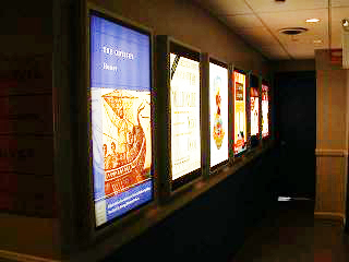 the gallery of posters in light boxes in the public hallway - after